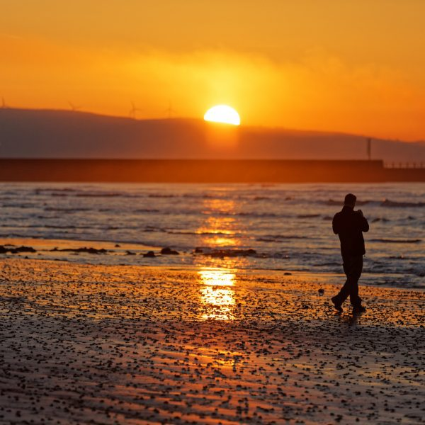 The sun rises over Swansea Bay in south Wales, UK